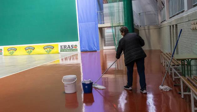El conserje seca aguas de unas goteras en el polideportivo