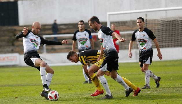 Ion Vélez intenta controlar el balón ante un jugador rival y sus compañeros Víctor Bravo, Lázaro y Lalaguna