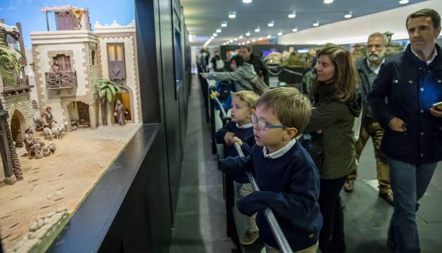 Unos niños miran con atención uno de los belenes que se pueden visitar en la sala del Baluarte.
