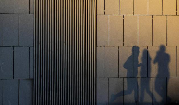 Tres siluetas se proyectan sobre un edificio en un atardecer otoñal en Pamplona