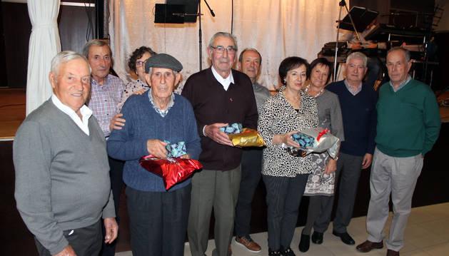 Los tres homenajeados mayores de 85 años, en el centro de la fotografía con sus obsequios.