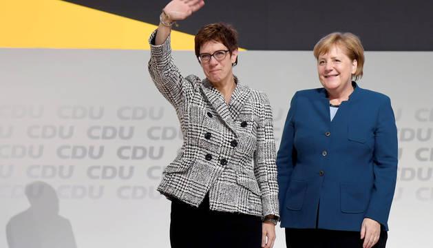 Annegret Kramp-Karrenbauer saluda junto a Angela Merkel.