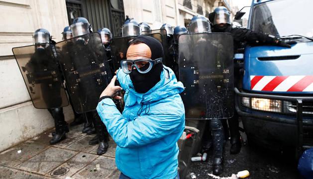 Un manifestante ante una barrera de agentes de policía en París.
