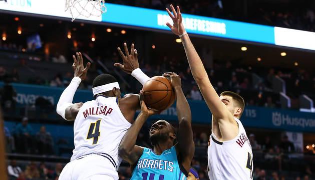 Juancho Hernangómez (dcha.) trata de frenar la internada del jugador de los Hornets, Michael Kidd-Gilchrist