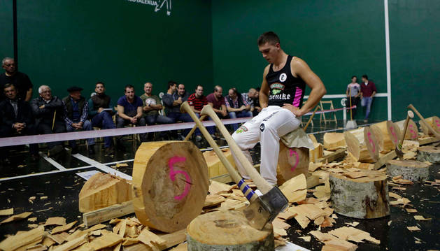 Iker Vicente, junto con todos los troncos que cortó en el último campeonato navarro de aizkolaris de primera que se disputó en el frontón de Santesteban.