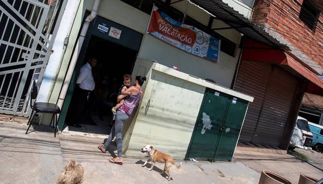Una mujer entra con su hijo en la Unidad Básica de Salud Jardim Vitória, en el