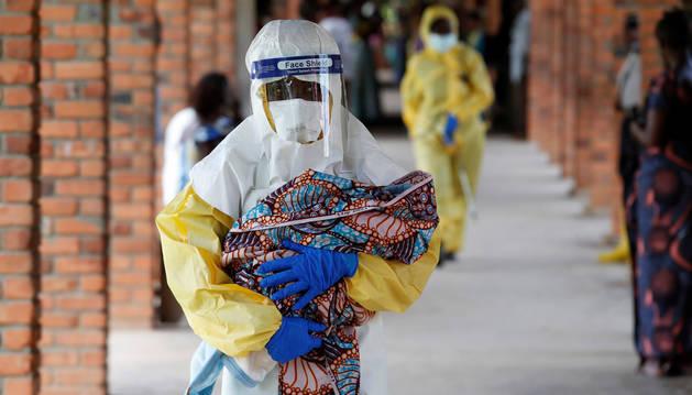 Un sanitario porta a un bebé sospechoso de estar infectado con ébola en el Congo.