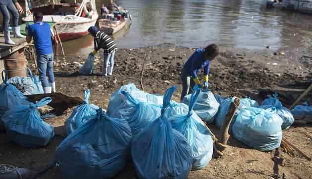 Voluntarios anudan parte de las bolsas con los restos de plásticos recuperados del río Nilo.