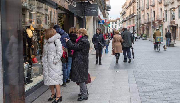 Varias personas miran un escaparate en la calle Carrera.