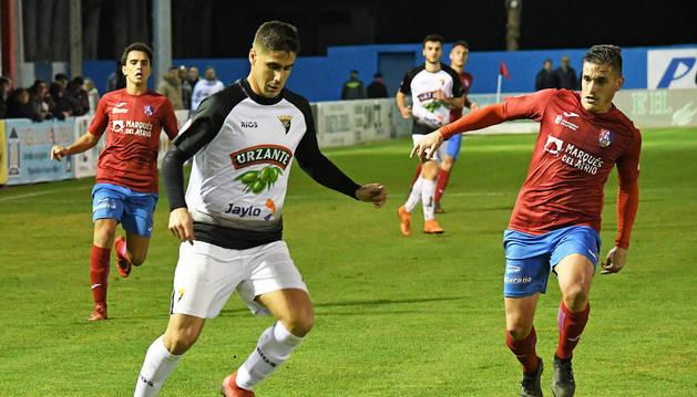 El jugador blanquillo Diego Royo conduce el balón ante la presión de un rival del Calahorra.