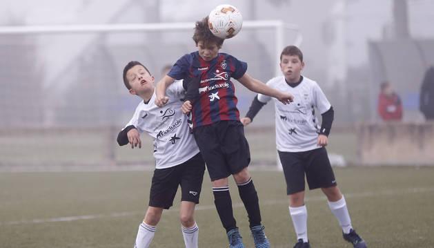 Un jugador del Mendigoiti, con camiseta azulgrana, trata de rematar de cabeza ante la presión de un futbolista del Sagrado Corazón, de blanco. Detrás, un compañero sigue la jugada.