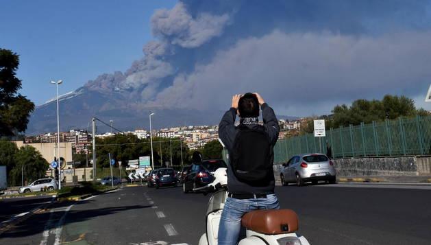 Un hombre toma una fotografía del volcán Etna en erupción.