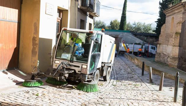 Una máquina barredora limpia en la calle Caldereros de Tudela, junto a la iglesia de la Magdalena.