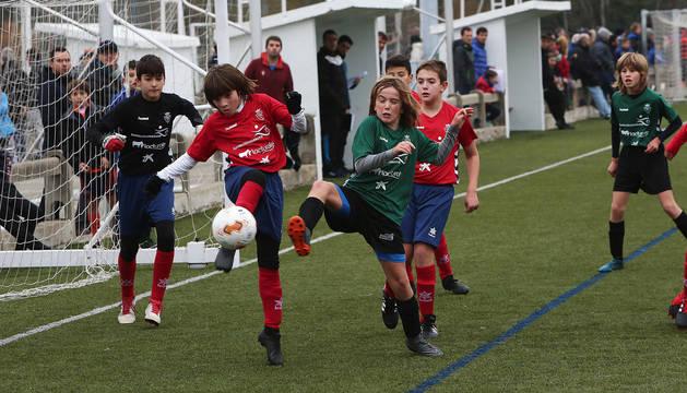 El defensa del Ángel Martínez Baigorri despeja un balón peligroso, mientras que un jugador del Hegoalde intenta cortarlo.