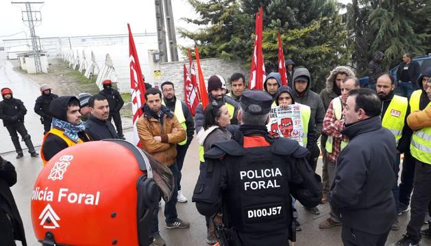 Imagen de varios trabajadores junto a agentes de la Policía Foral, en el entrada a la empresa Huertas de Peralta.