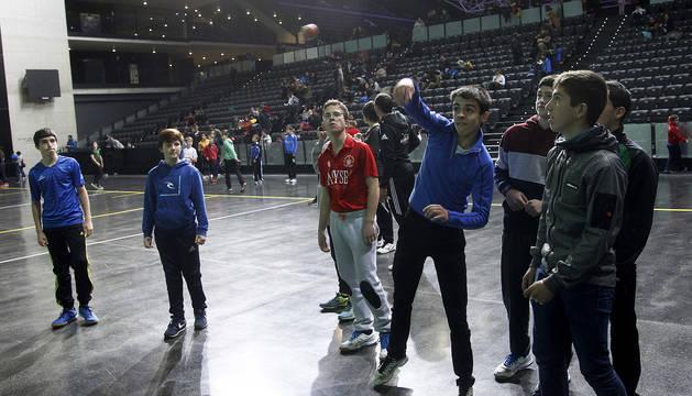 Un grupo de participantes observa a uno de ellos golpear la pelota en el frontón del Navarra Arena.