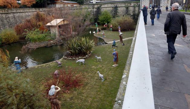foto de Un hombre camina junto a los fosos de la Taconera, en el estanque de 'los patos' donde está instalado el belén.