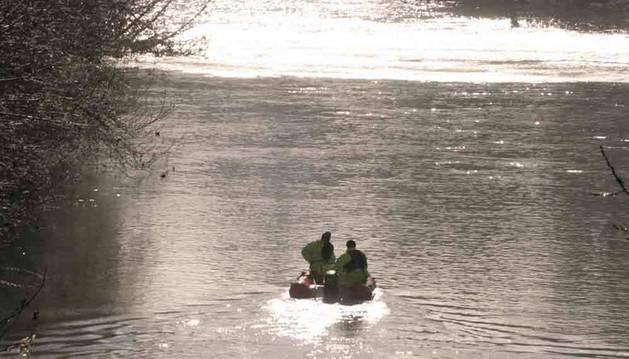 Bomberos y el helicóptero, durante una búsqueda en el río Arga, a su paso por Pamplona.