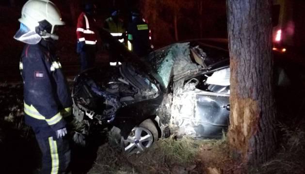 Un bombero observa el coche, que quedó empotrado contra un árbol. Ni rastro del conductor.