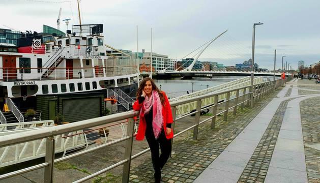 Marta Domínguez, en un embarcadero del río Liffey; al fondo, el puente Samuel Beckett, diseño de Calatrava.