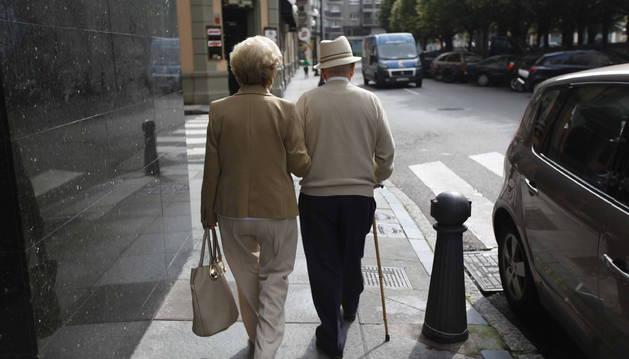 Dos pensionistas paseando por la calle.