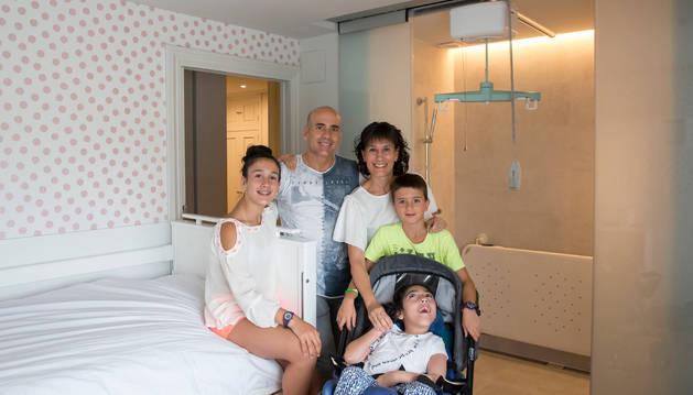 Foto de Anne Erice con su familia, en la habitación adaptada de su casa.