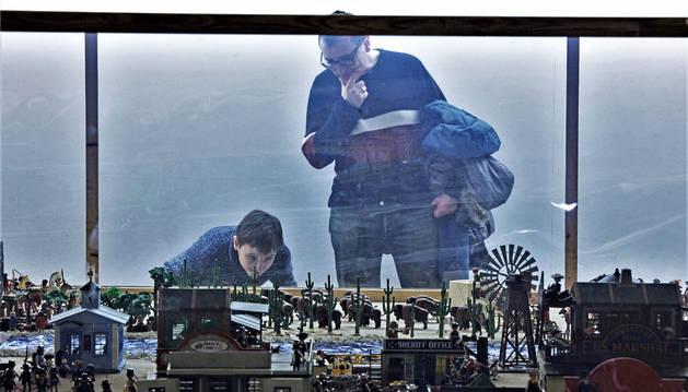 Foto de un niño observa con detalle el diorama de clicks dedicado al salvaje oeste.