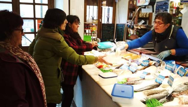 Foto de un grupo de vecinas de Lumbier compra en la pescadería de Inma Ducay empleando 'tuppers'.