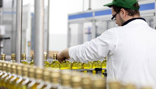 Foto de un empleado de una industria agroalimentaria maneja una cinta de embotellado.