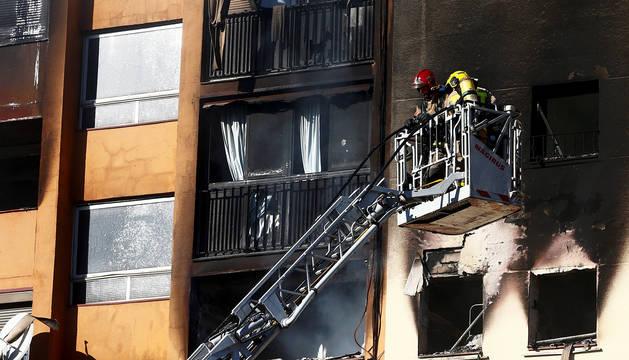 Los bomberos trabajan en la extinción del edificio incendiado en Badalona.