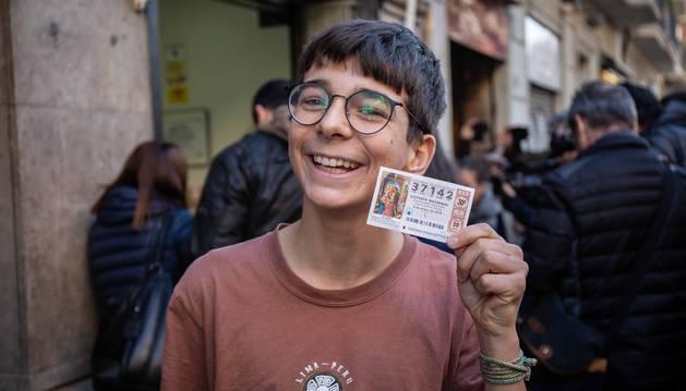Foto de uno de los premiados en la administración 271 de Barcelona donde ha caído íntegramente el primer premio del Sorteo Extraordinario de El Niño.