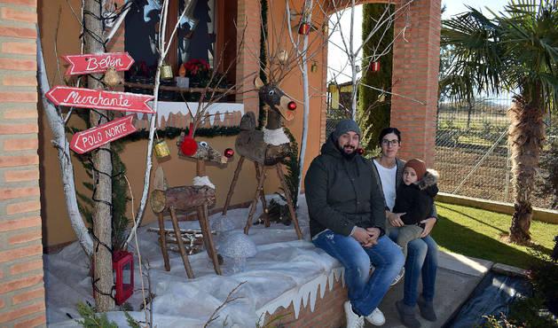 Rosa Jarauta, junto a su pareja Sergio Escribano y su hijo Noah, ante la decoración navideña de su casa.