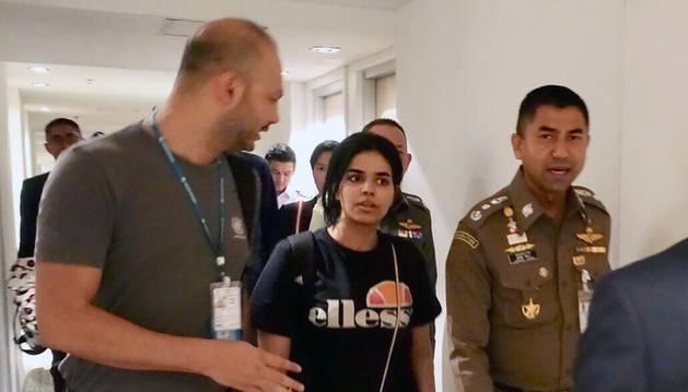 La joven saudí, Rahaf Mohammed Al-Qunun (c), conversa con el jefe de la policía de inmigración de Tailandia, Surachet Hakparn (d), y un trabajador de ACNUR (i) antes de abandonar el aeropuerto Suvarnabhumi en Tailandia.