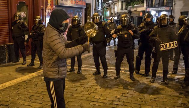 foto de Un joven golpea una cazuela delante de la policía.