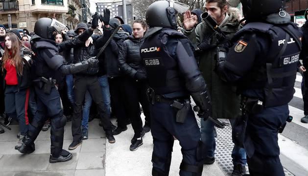 Efectivos de la Policía Nacional disuelven una concentración que han llevado a cabo un centenar de jóvenes junto al Parlamento de Navarra donde han acudido para protestar por la intervención de la Policía Foral esta madrugada en el palacio del Marqués de Rozalejo.