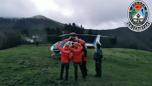 Agentes de la Ertzaintza buscan en un helicóptero a los tripulantes desaparecidos.