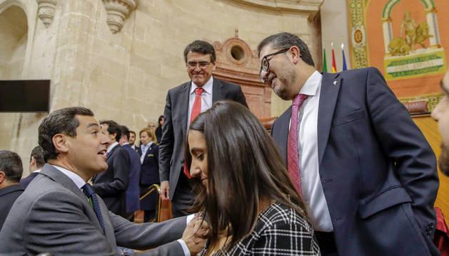 El líder del PP-A, Juanma Moreno (i), y el juez Francisco Serrano (d), cabeza de lista de Vox, se felicitan mutuamente en el Parlamento de Andalucía en Sevilla el pasado 27 de diciembre.