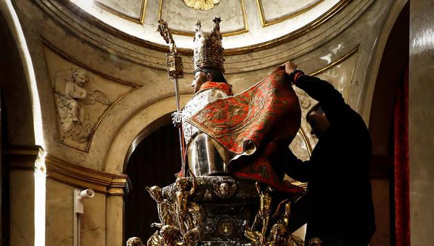 Enrique Bretos Noáin, miembro de la Corte de San Fermín, se dispone a cambiar la capa de la imagen del santo, para la procesión de 2017. Es una de las tareas de los cofrades.
