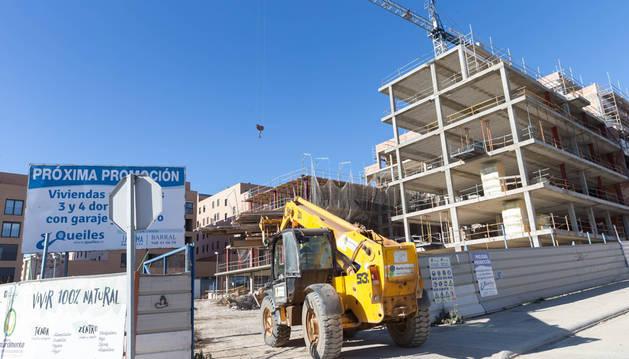 Una máquina entra en la parcela del paseo de los Poetas de Tudela donde se están construyendo 42 pisos.