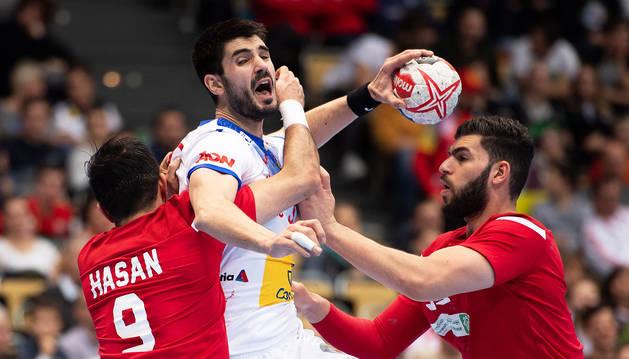 Eduardo gurbinod busca el lanzamiento ante los jugadores de Bahrein, Hasan Madan (dcha,) y