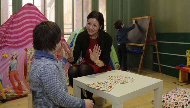 La pedagoga Inma González Undiano, de 44 años,  choca las palmas con Álvaro Morrás Ovelar, de 8 años y con Síndrome de Down, en la sede de la asociación D-Espacio, en el edificio del Seminario.