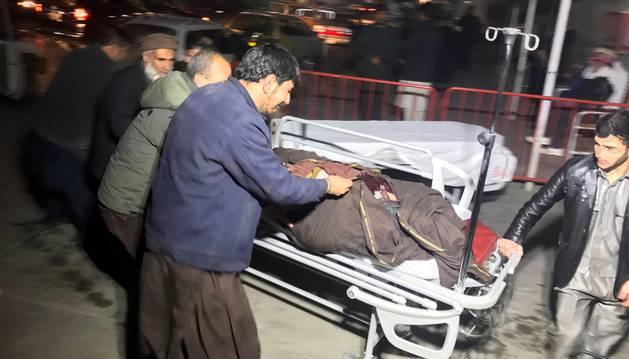Varios hombres trasladan a un herido tras un atentado con coche bomba en Kabul (Afganistán).