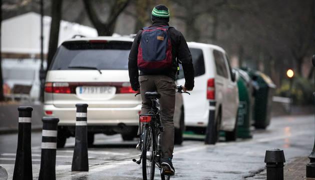 foto de Un hombre en bicicleta, durante una jornada lluviosa en el Paseo Sarasate de Pamplona.