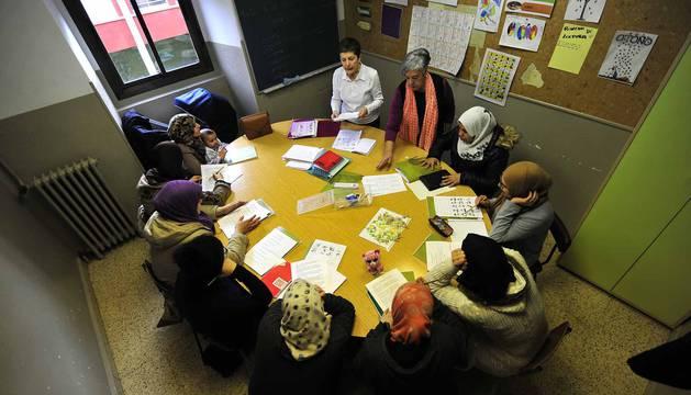 Dos voluntarias imparten clase a uno de los grupos más numerosos de las clases de alfabetización.