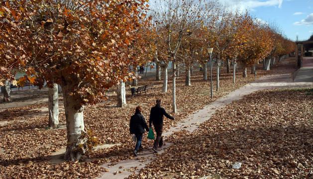 Una pareja camina por el Paseo del Prado.