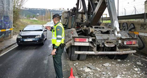 Imagen de la Guardia Civil regulando el tráfico tras el choque de la grúa -a la derecha- con el puente.