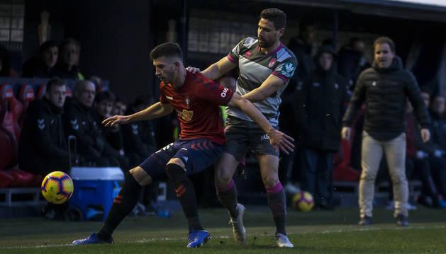 David García protege el balón ante l presencia de un jugador del Granada.