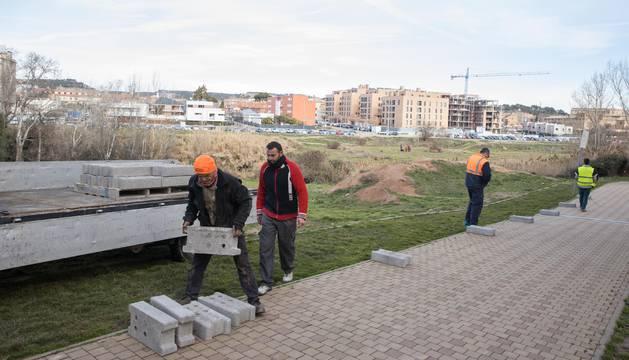 Foto de operarios de la adjudicataria comienzan a colocar material de obra en el paseo.
