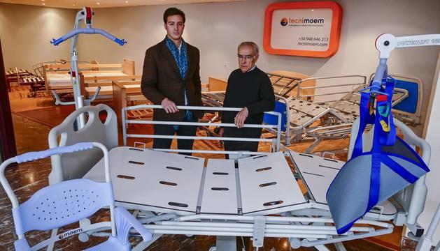 Foto de Jaime Arriazu (izquierda) y Pablo Brau, gerente y dueño de Tecnimoem, respectivamente, con productos que salen de la fábrica en Viana: camas articuladas de diferentes características, arnés, sillas de baño, grúa...