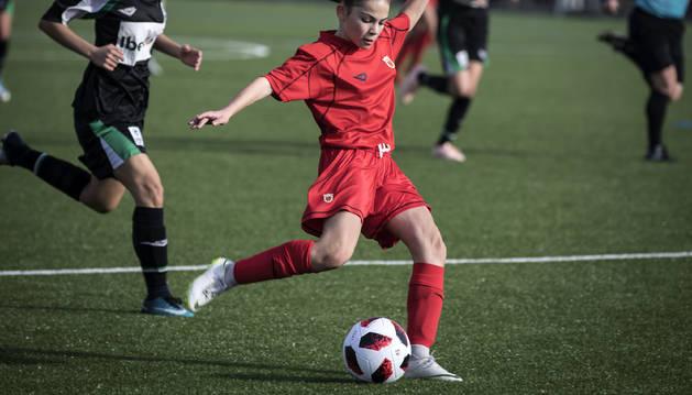 Una jugadora de la selección navarra sub-15 conduce el balón ante una rival.